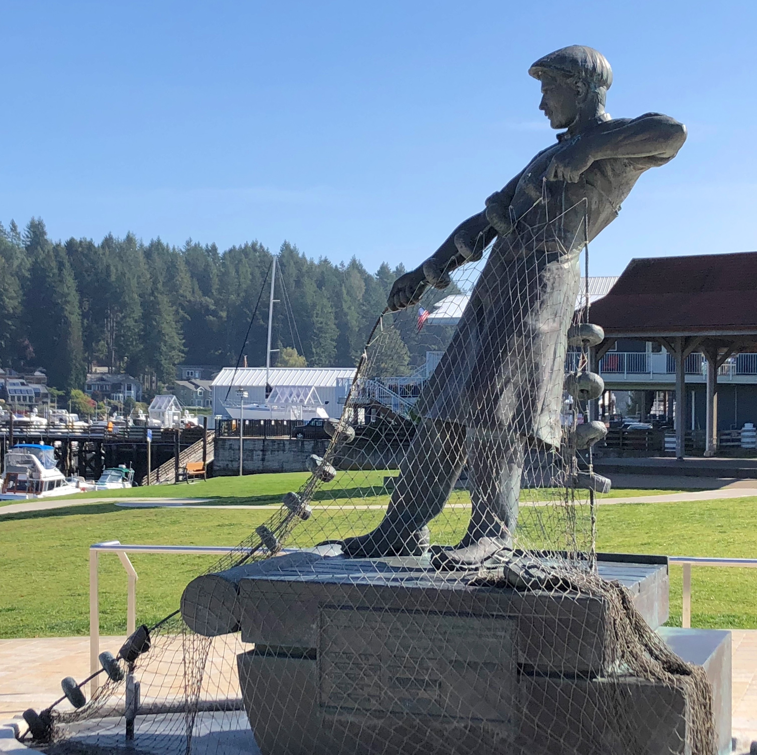 A statue at the park next door to Gig Harbor Marina shows a fisherman reeling in a net.